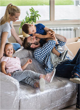 Family sitting on a couch rough housing in a house they are moving into.