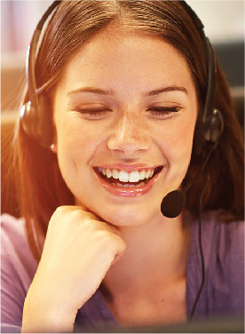 Woman on a headset smiling in front of a computer.
